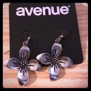 Two silver tone earrings from Avenue that dangle.